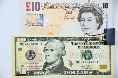 stapled: british pounds and us dollars banknotes stapled together