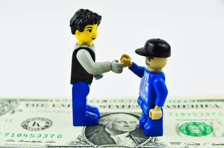 deal making: two toy guys making financial deal with dollars