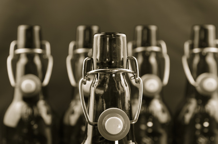 straight up: Empty beer bottles  stand straight up in one row, shallow DOF Stock Photo