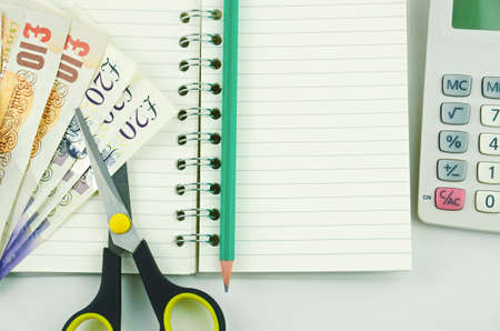 cutting costs: A note book with pencil and calculator, counting costs Stock Photo