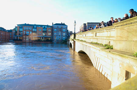 tragedies: Flooded York by river Ouse in Yorkshire UK at december 2015. People observe  river from bridge