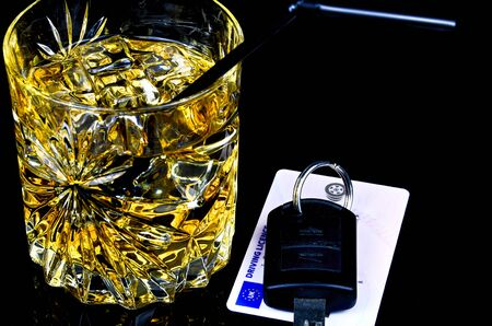 dont drink and drive: Close-up of car keys with unfinished alcohol drink on table. Dont drink and drive. Stock Photo