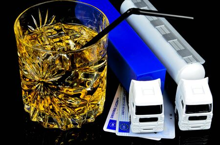 dont drink and drive: Close-up of unfinished alcohol drink and two lorrys. Dont drink and drive. Stock Photo