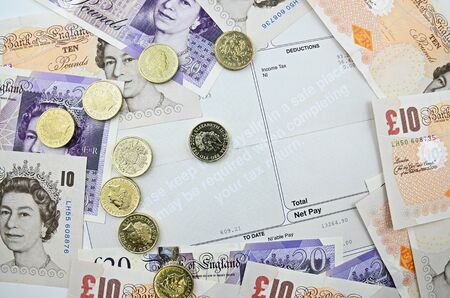 payslip with british  banknotes and coins