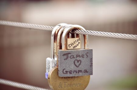 keylock: Padlock in the form of hearts hanging on the bridge next to the other locks. Stock Photo