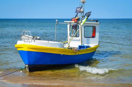 White yellow blue   fishing boat on alongshore