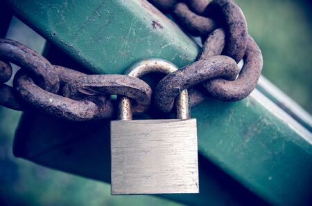 chaining: Rusty padlock on rusty chain