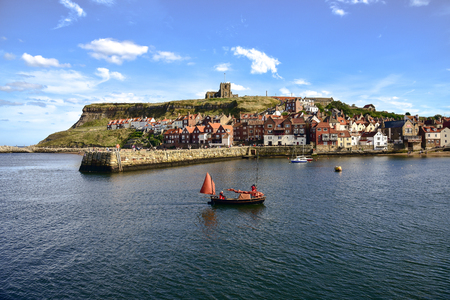 View of boat returning to Whitby Harbour and gothic church in background