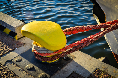 tied in: Rope tied in a knot on a bollard. Mooring rope wrapped around the cleat on sea background. Metal capstan in harbor for the mooring of yachts and boats Stock Photo