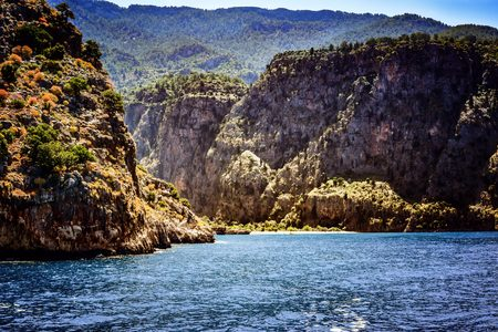 oludeniz: View of Butterfly Valley from a sailing boat with bright sea and high mountains.