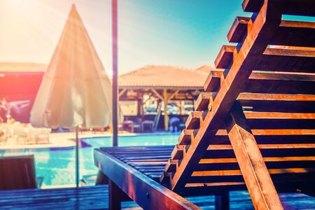 Wooden sun beds with umbrella against swimming pool in holiday resort
