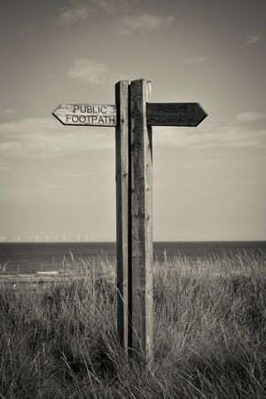 wooden post: Old wooden  sign on the beach in Spurn Point near Hull UK