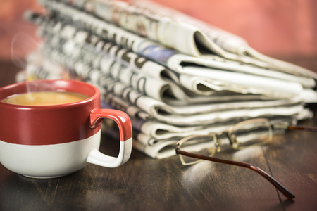 Stack of newspaper on wooden background with cup of coffee and glasses Stock Photo