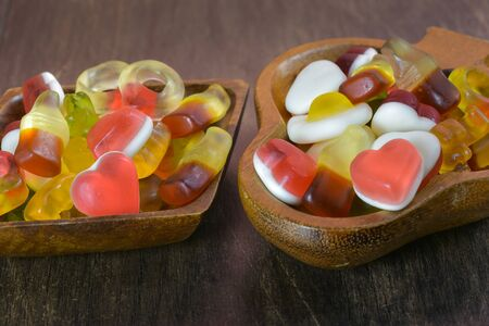 Bowl with Gummy Candy (selective focus) on wooden background