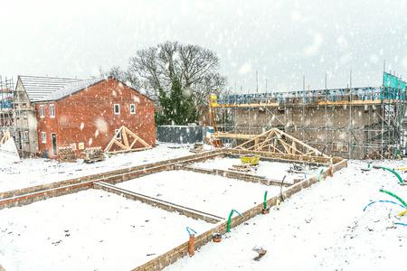 겨울 시간 동안 새 벽돌 집을 짓고있는 건설 현장, 눈이 내리는 조건