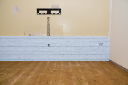 White brick wall renovation with wall holder for TV