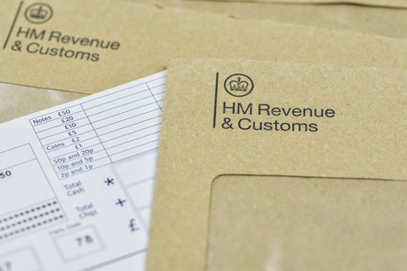 England, UK - August 16 2018: The logo of Her Majestys Revenue and Customs on envelope, with money or check included inside.  HMRC is a non-ministerial dept of the UK Government.