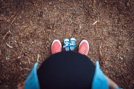 Family together with baby shoes and standing the summer park. View from top to bottom