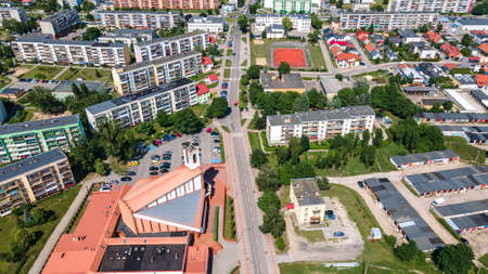 The mix of different photos taken from drone in Ilawa town in Poland, there is a church, lake Jeziorak, house estate, swimming pool, amphitheater, railway depot, sailing harbor, forest island, hospital etc.