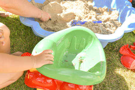 Child boy with mom play construction vehicle toy in sand playground bucket, construction industry