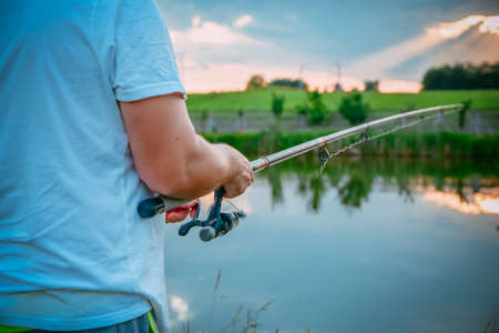 Young man fishing on lake at sunset enjoying hobby. Outdoor, activity. Narrow focus. Stock Photo