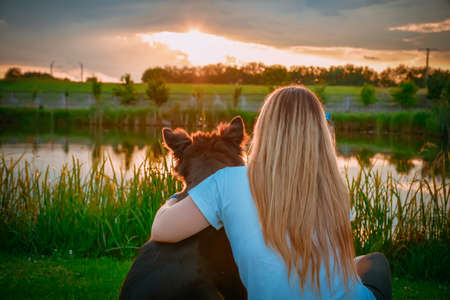 Zabrowo, Poland - June 08, 2020: Capture a young girl with her dog watching sunset near the pond