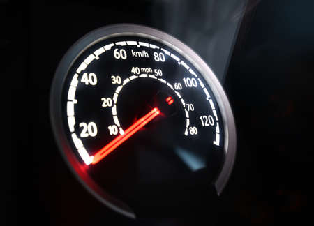Specific speedometer on dark background. It comes from HGV truck dashboard, blurred, miles and kilometers