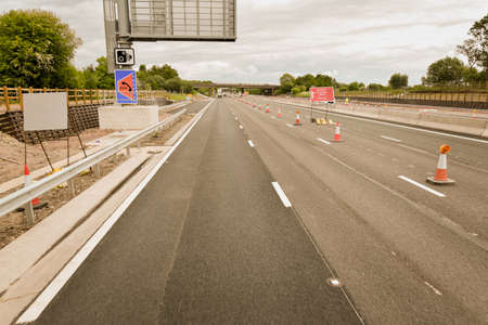 Ongoing road works and moving traffic on motorway M62 in England. Show speed limit