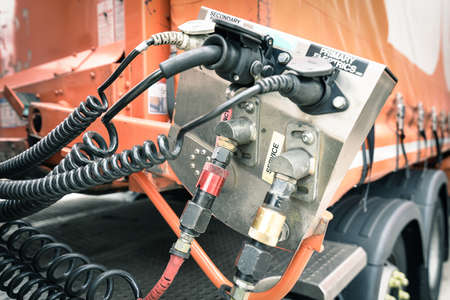 Back wall of a  industrial tractor cab with high-pressure connecting hoses and connecting devices with valves for the correct operation of big rig semi truck pneumatic systems.