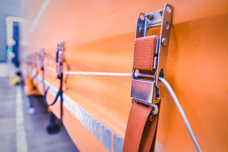 A tie down strap holding steel security cord. Ratchet strap on orange truck curtain. Banque d'images