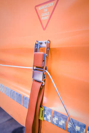 A tie down strap holding steel security cord. Ratchet strap on orange truck curtain.