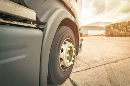 Close up for cab of a lorry with a view of big tyre in sunny day Banco de Imagens
