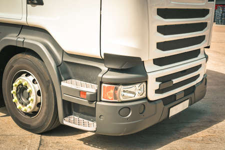 Close up for cab of a lorry with a view of big tyre in sunny day Stock Photo