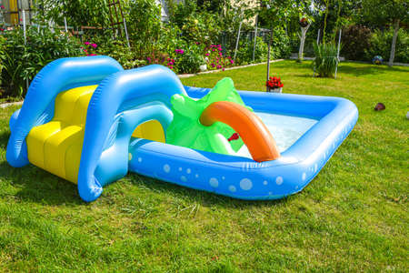 A summertime garden with inflatable swimming pool in the background Foto de archivo