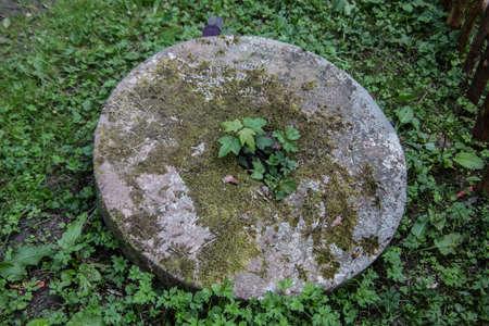 Stone mill wheel in the grass 版權商用圖片