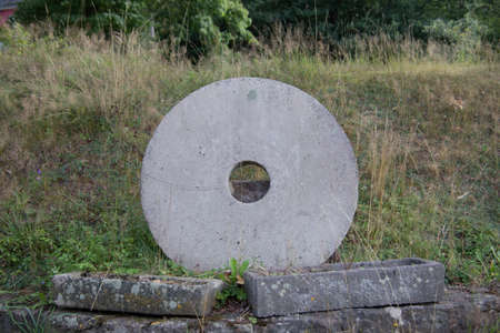 heavy stone mill wheel stands in the grass