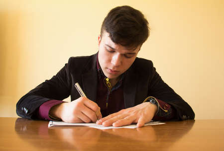 signing authority: The young businessman signs the documents