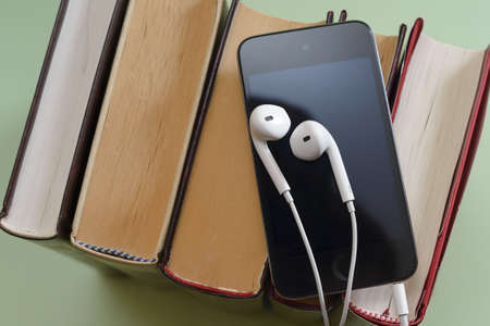 Phone with white earpods on stack of books audiobook storytel podcast music concept