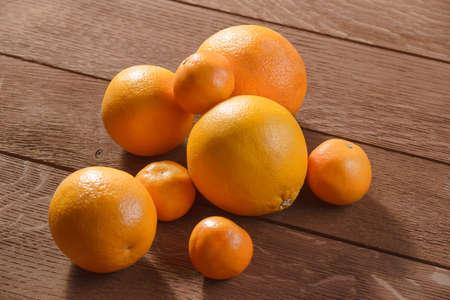 Orange and mandarines fruits on old wooden background copyspace