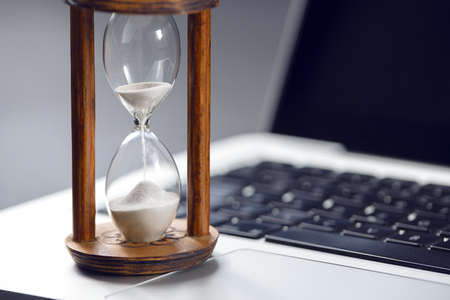 Hourglass as time passing concept for business studying deadline, urgency and running out of time.
