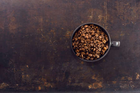 Coffee beans in coffee cup on background