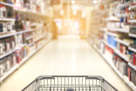 Supermarket aisle with empty shopping cart abstract blur copyspace textspace 스톡 콘텐츠