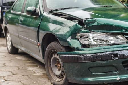 Car crash or accident. Front fender and light damage and scratchs on bumper. Broken vehicle detail or close up.