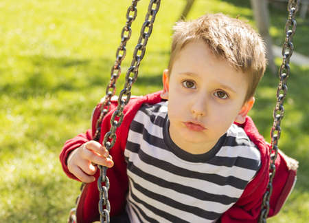 Child make the swing in the playground  Stock Photo