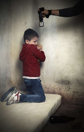 degradation: Abused child, curled up on a mattress in the middle of dirt gets beaten up by drunk and abusive parent  Stock Photo