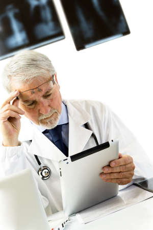 Doctor in clinic sitting at desk looking at x-rays on tablet, white background with x-rays.