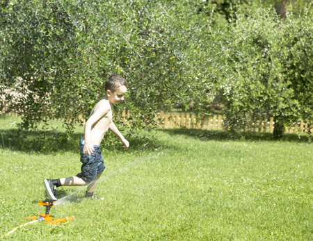 Happy Child Playing with Water in the Garden  Stock Photo