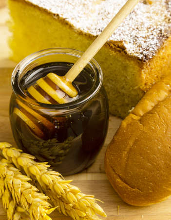 Healthy jar of honey with bakery products on wooden background  photo