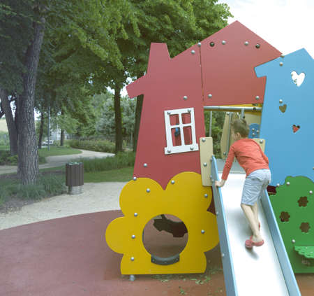 July 5 2013 S.Egidio, Italy - Child playing with the slide in the playground on a beautiful sunny day.