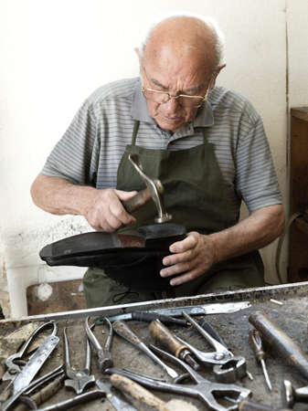 intent: Old shoemaker adjusts the sole of a shoe